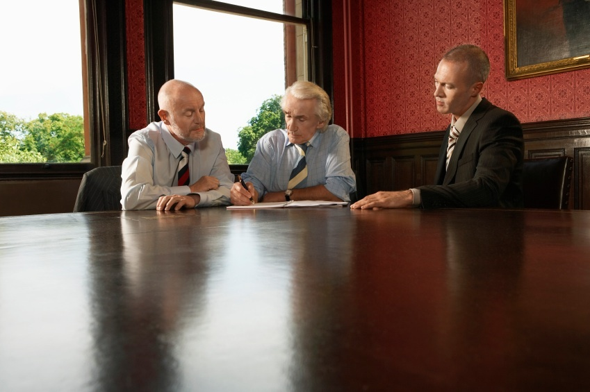 Businessman With Male Colleagues Signing Contract